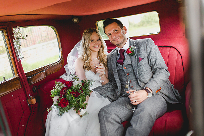 bride and groom in the back of wedding car
