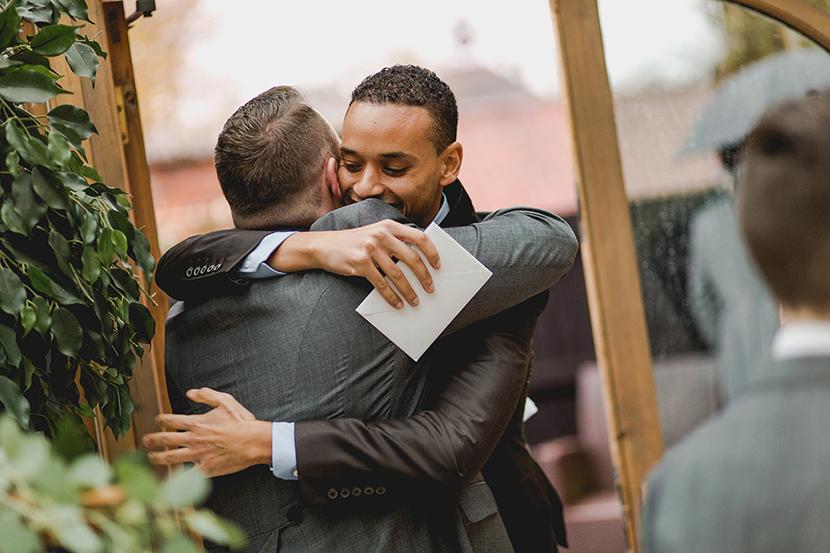 friends hug at wedding