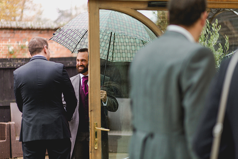 groom greets guests in the rain