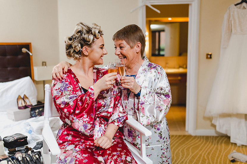 mum and bride enjoy champagne together