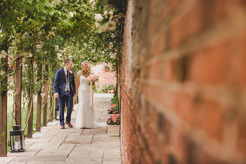 couple holding hands next to a brick wall