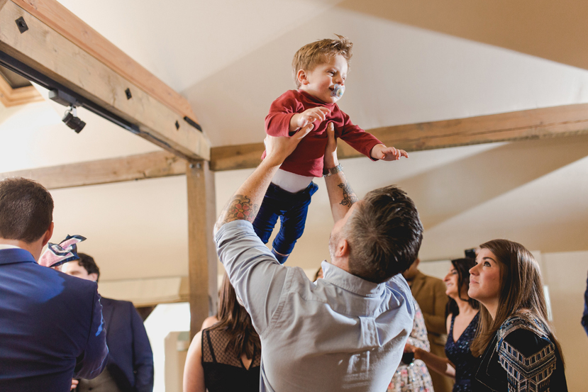 baby being thrown in the air at wedding