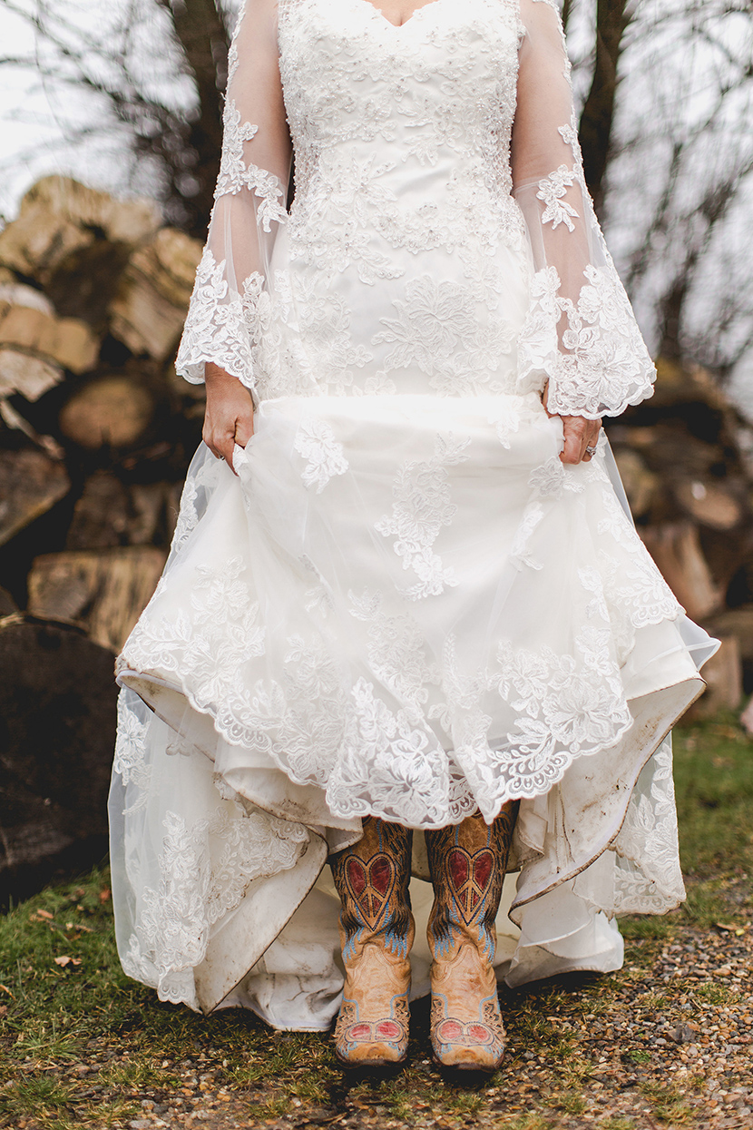 bride lifting wedding dress to show cowboy boots