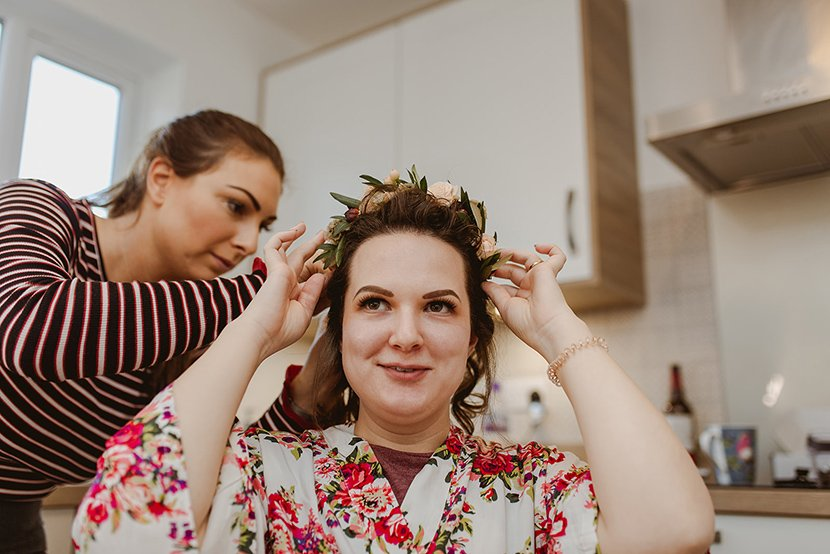 bride putting on flower crown during prep