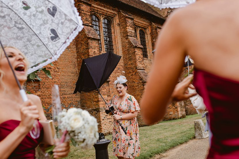 wedding guests laugh as their umbrellas are turned inside out by the wind