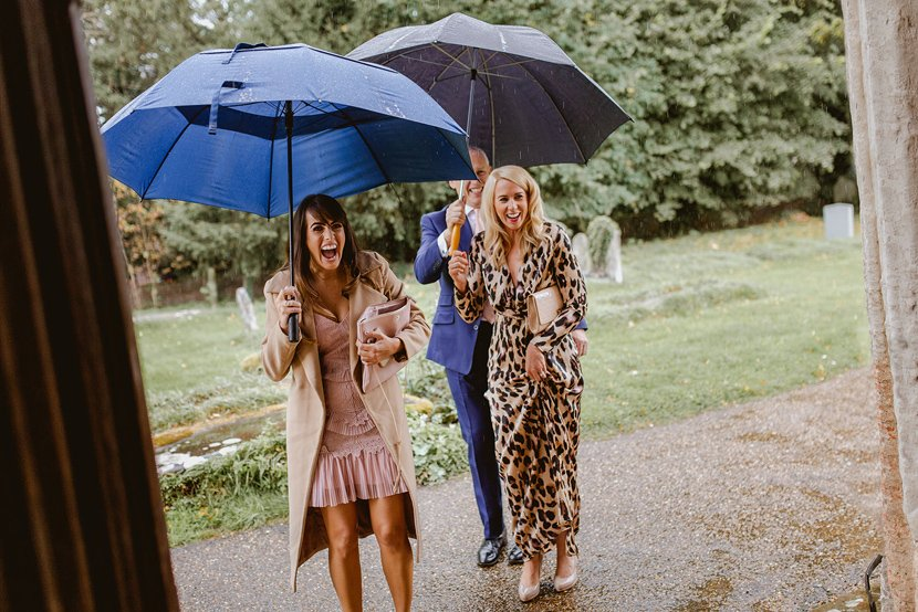 excited wedding guests arrive to the wedding ceremony with umbrellas as it is raining
