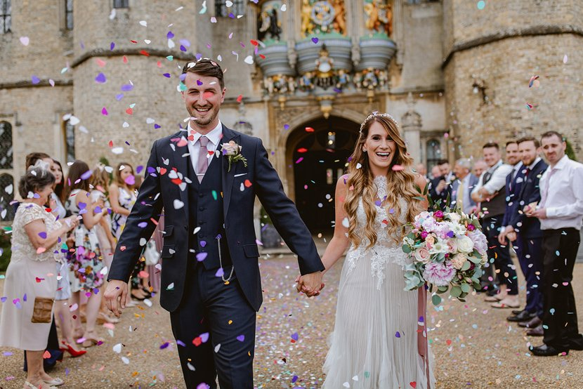 bride and groom walk through tunnel of multicoloured confetti at Hengrave Hall in Suffolk