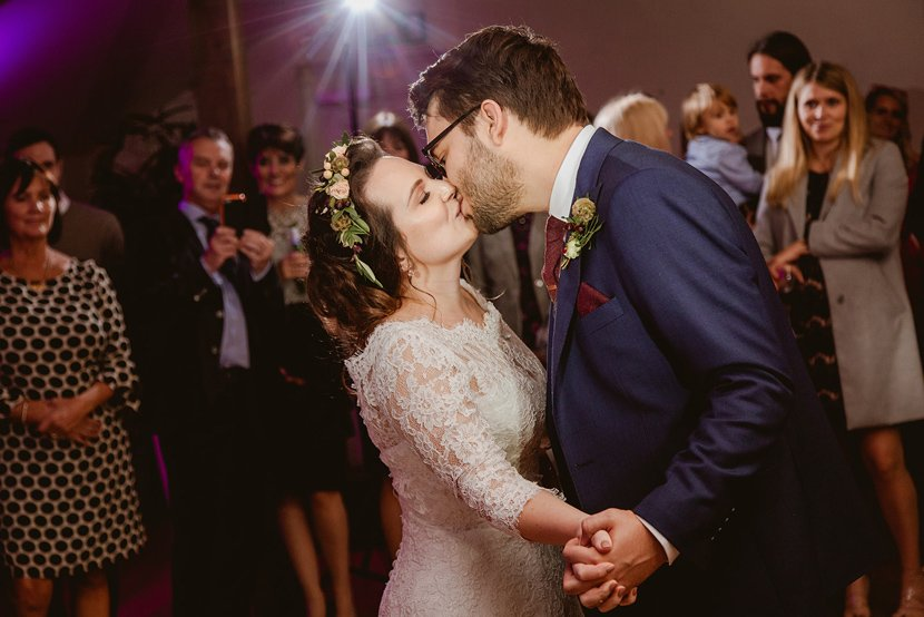 bride wearing a flower crown and her groom lean in and kiss during their first dance