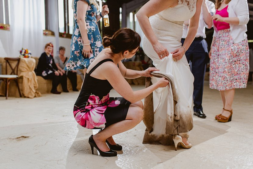 wedding guest helps bride to pin up her wedding dress which is caked in mud