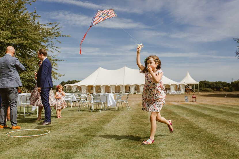 little girl runs flying a kite at a summer wedding with marquee in the background
