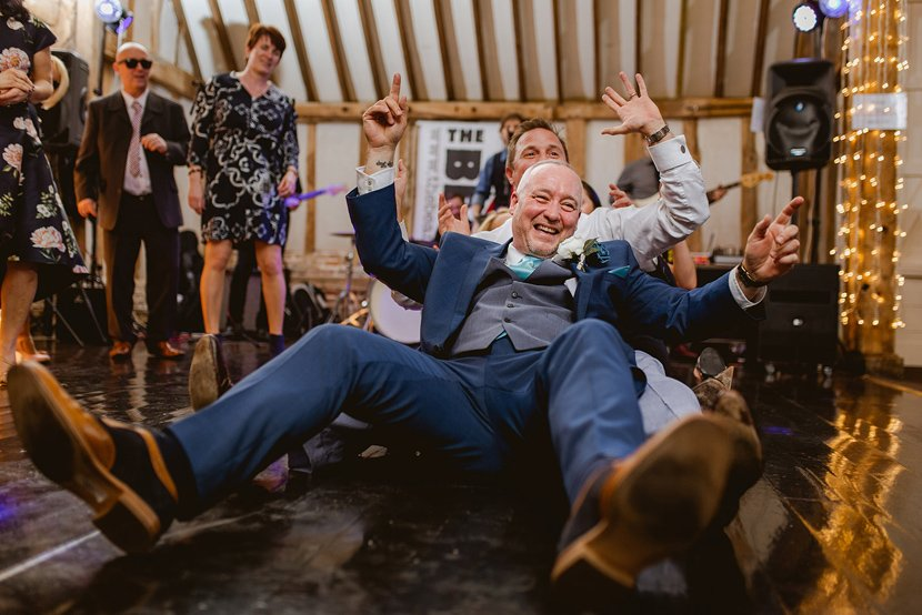 groom and wedding guests sit on the floor to dance during party at wedding