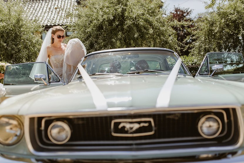 cool bride wearing sunglasses gets into her wedding car, a classic vintage ford mustang