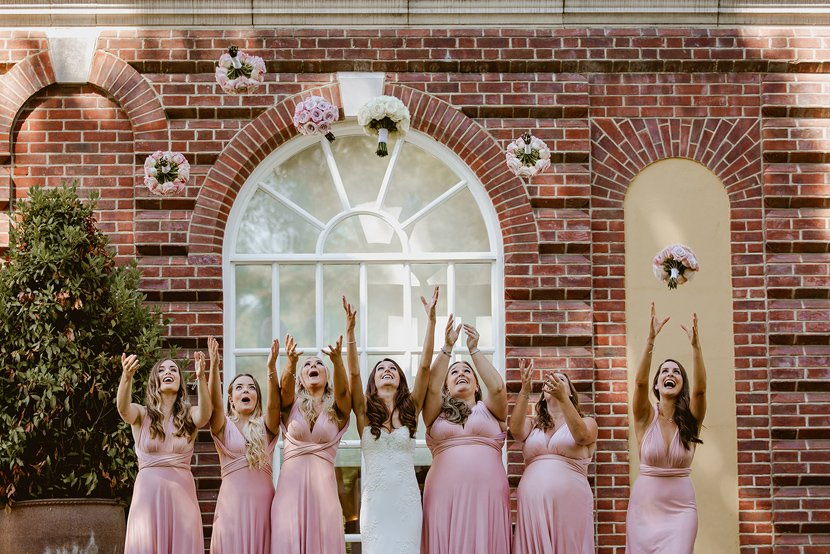 bride and her bridesmaids in pink bridesmaid dresses throw their bouquets in the air at a wedding
