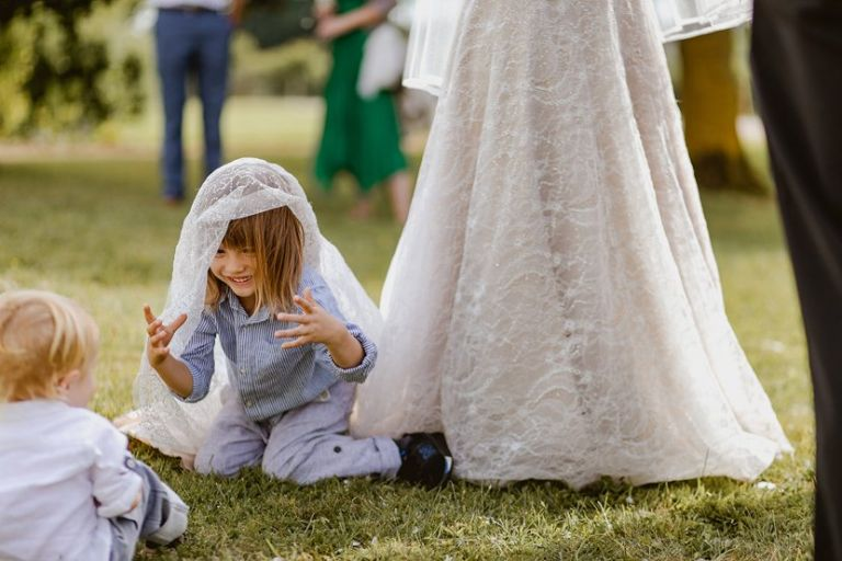 cheeky little boy plays in the train of brides wedding dress