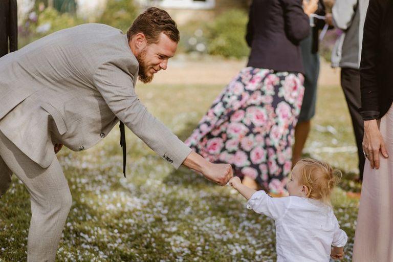 man fist bumps toddler at a wedding