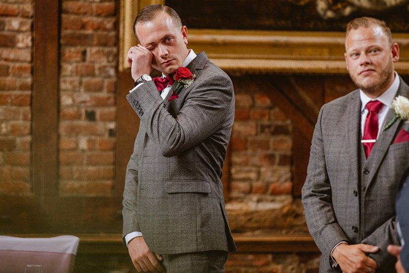 emotional groom wipes away tears as he sees his bride for the first time