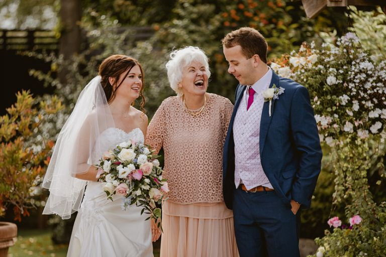 bride and groom share a happy moment with grandmother during family photos at a wedding
