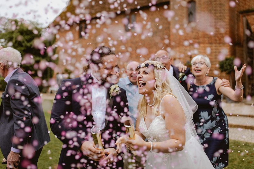 excited bride and groom let off pink confetti cannons as part of their wedding gender reveal celebrations