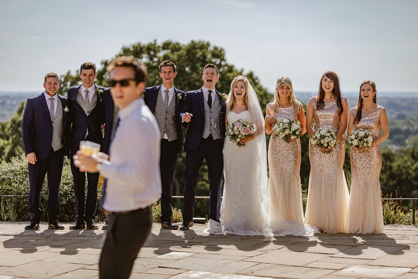 man wearing sunglasses and holding a pink of beer accidentally walks in front of the camera during group photographs at a wedding
