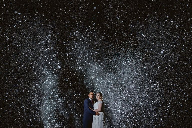 bride and groom hugging against a dark night sky with snow falling