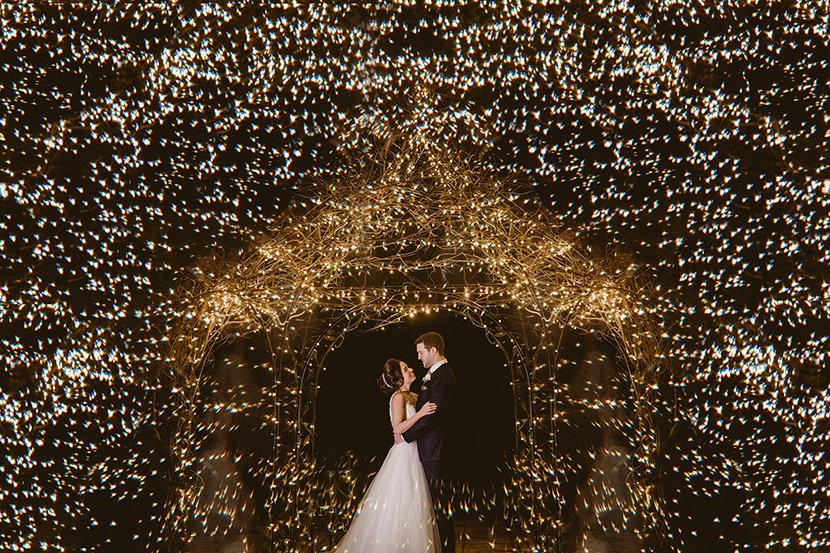bride and groom standing under a wedding gazebo full of fairy lights for their New years eve wedding at Gaynes park
