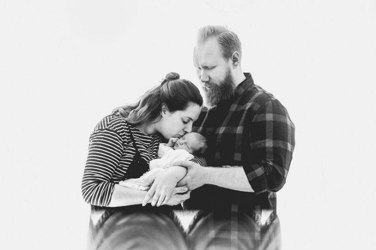 new parents kiss baby on forehead
