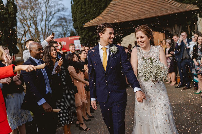 Bride and groom walk and smile during confetti photo for their wedding at the old parish rooms