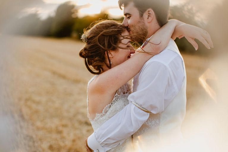 bride and groom kiss on forehead