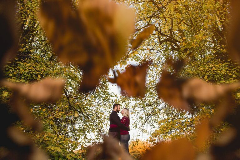 bride and groom to be between leaves