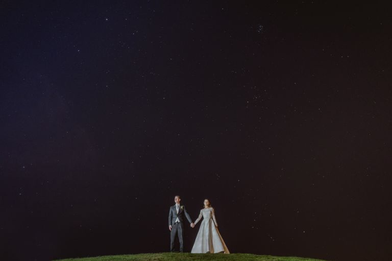 bride and groom holding hands under stars